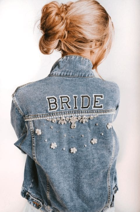 Bride wearing a hand painted funky, edgy denim jacket